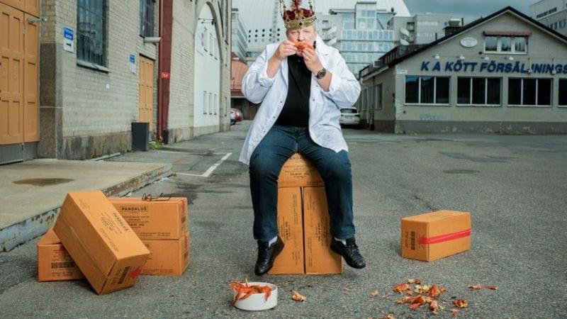 Man med kungakrona på huvudet sitter på en kartong i ett industriområde och äter kräftor
